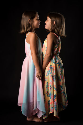 Side view of girl standing with sister on black background