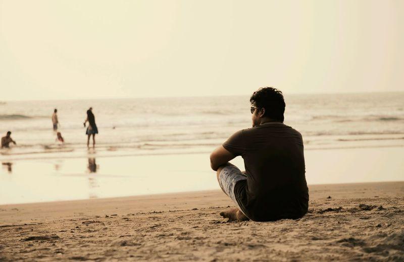 Man sitting on beach against clear sky