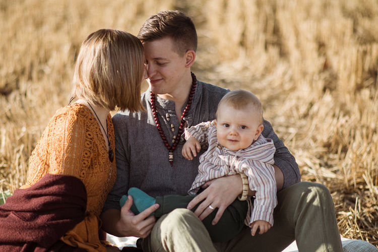 Couple with son kissing while sitting on land