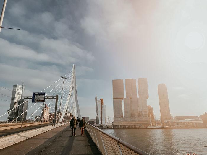 Rear view of people on bridge against sky