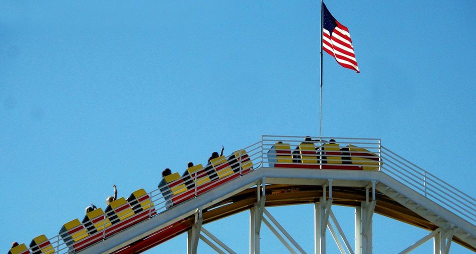 Low Angle View Of American Flag On Rollercoaster Against Clear Blue Sky