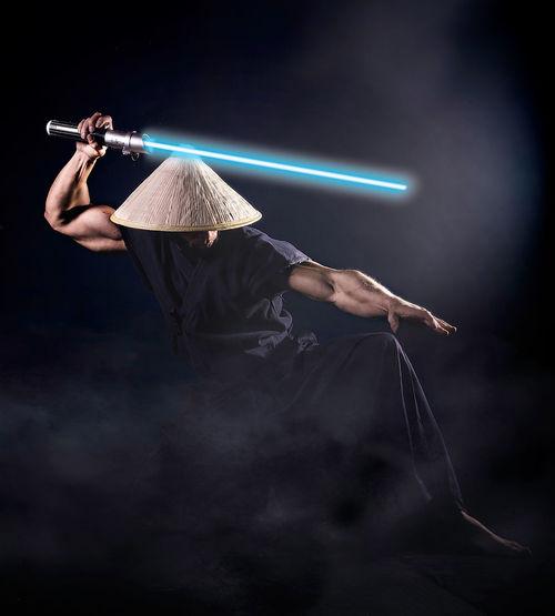 Muscular man holding laser sword against black background