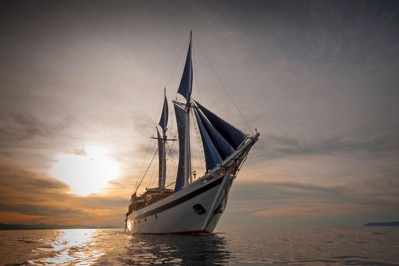 """Indonesian Schooner """"Ombak Putih"""". A traditional phinisi schooner working the Raja Ampat area of the east Indonesian archipelago. ASIA Boat Day INDONESIA Indonesia_photography Maritime Nautical Vessel No People Outdoors Phinisi Raja Ampat Sailboat Sailing Sailing Ship Schooner Sea Sky Southeast Asia Sunset Tall Ship Traditional Transportation Travel Travel Traveling"""