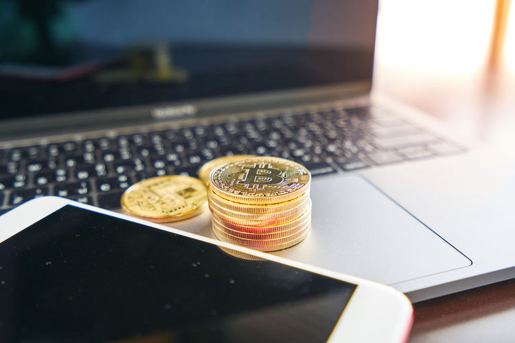 Close-up of coins and smart phone on laptop