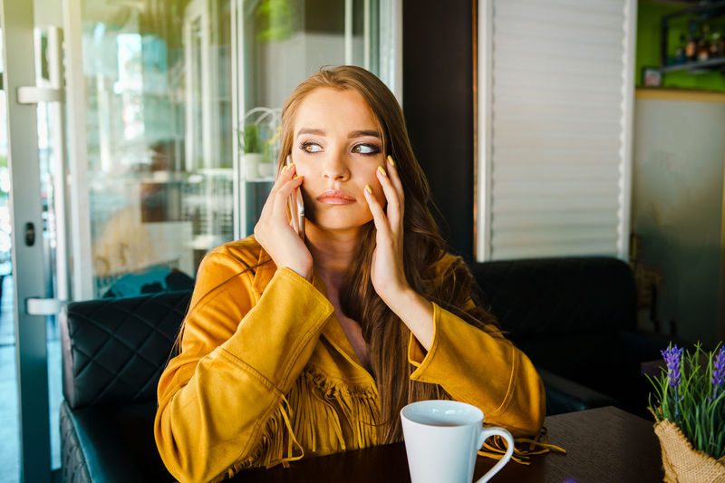 Portrait of young woman sitting on table at cafe