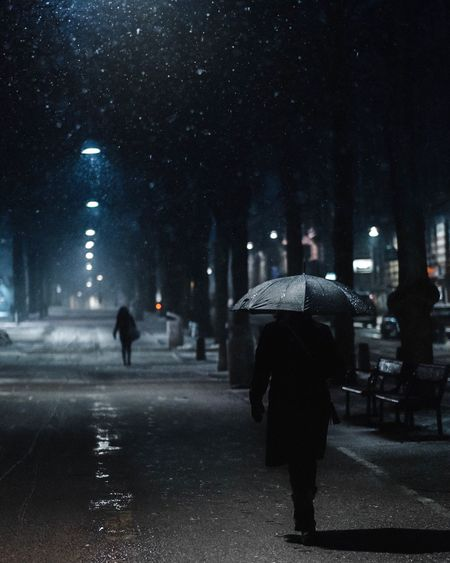 Rear view of people walking on wet road during winter