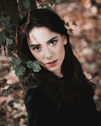 High Angle Portrait Of Beautiful Woman Leaning On Tree Trunk