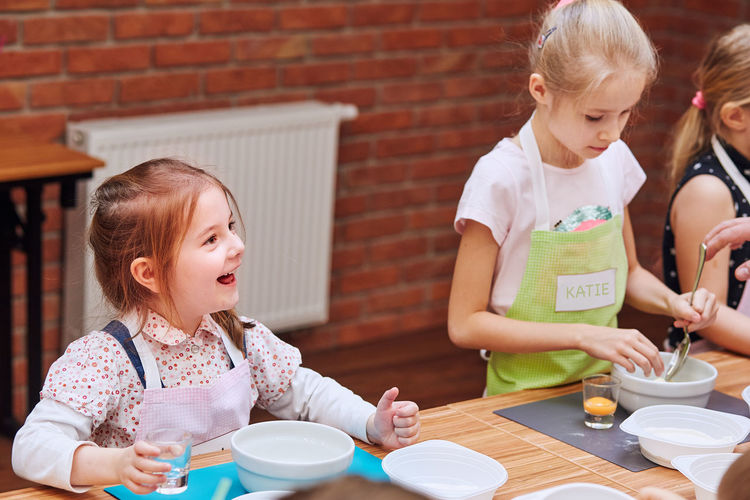 Girls preparing cake in classroom