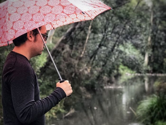 Midsection of man holding umbrella while standing in rain