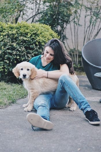 Portrait of woman with dog sitting outdoors