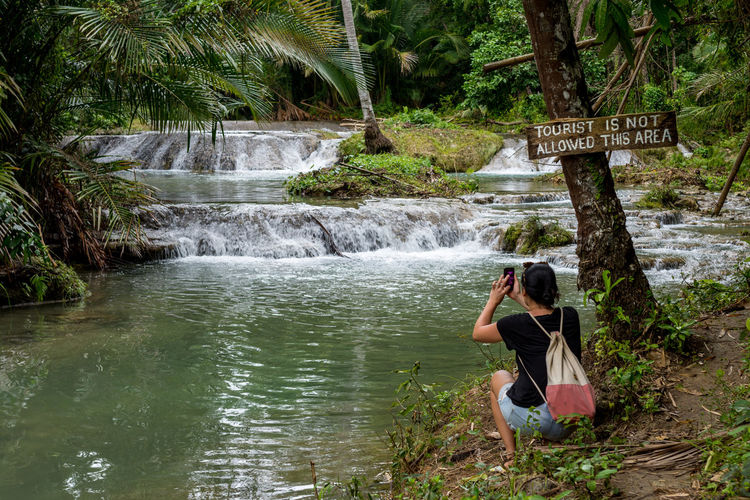 Woman photographing by stream