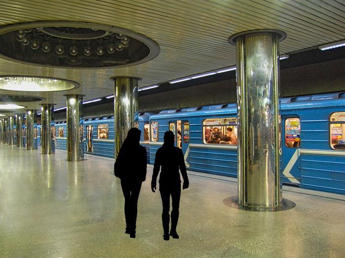 Rear view of people walking on illuminated underground walkway