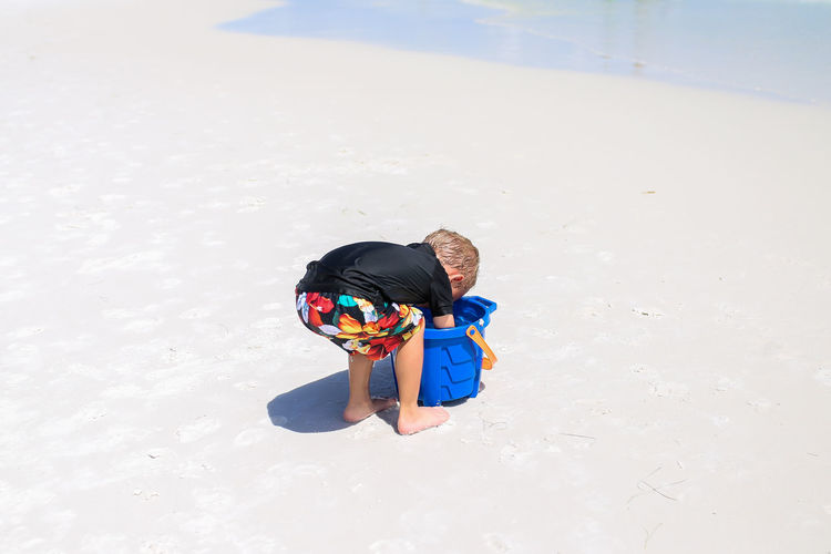 Young Boy Playing in Sand While Digging in Sand Bucket on Summer Vacation Child Leisure Activity Childhood Water Outdoors Full Length Boys Land Nature Day Beach Summer Summer Vacation Sand Beach Toys Sand Bucket Bucket Childhood Memories Beauty In Nature Little Boy Young Boy Beach Fun Beach Vacation Sand Toys Beach Bucket