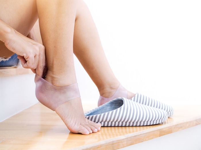 Low section of woman wearing silicone cover by shoe on steps