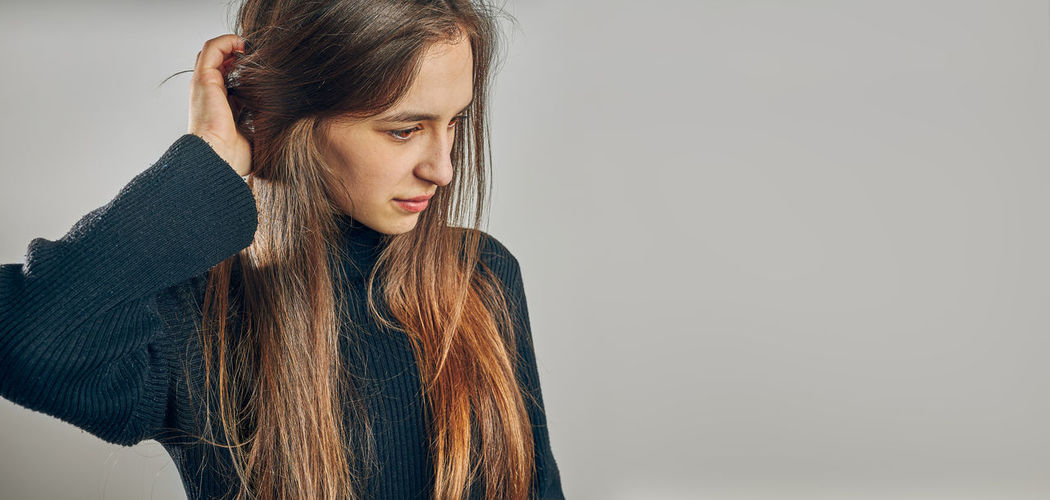 Young woman looking away against white background