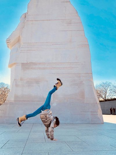 Girl doing handstand against built structure and sky
