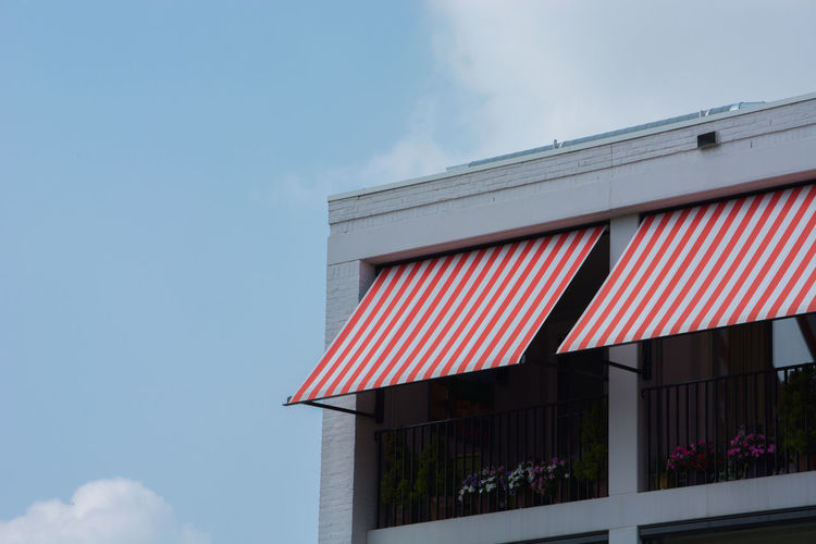 Low angle view of building with awnings against sky