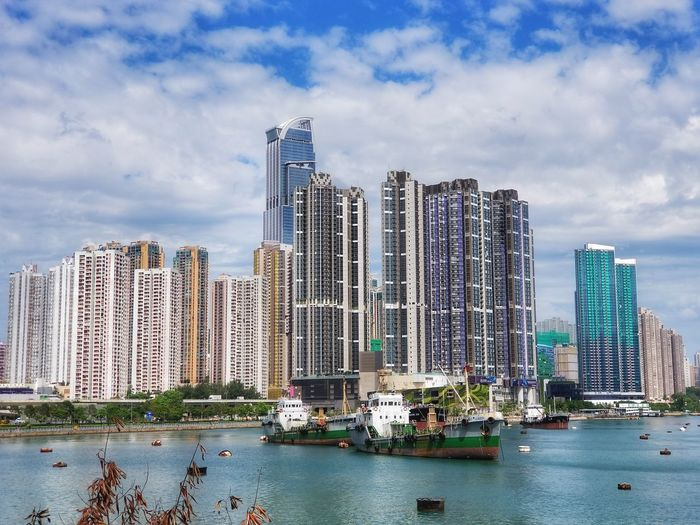 Modern buildings by lake against cloudy sky