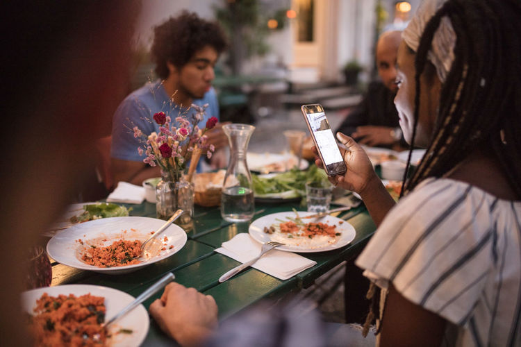 Young woman using mobile phone while having dinner with friends during garden party