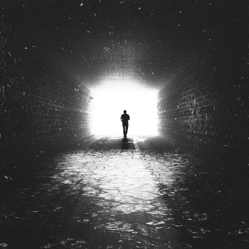 Rear View Of Silhouette Man Standing In Tunnel