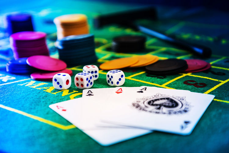Close-Up Of Cards By Dices And Gambling Chips On Casino Table