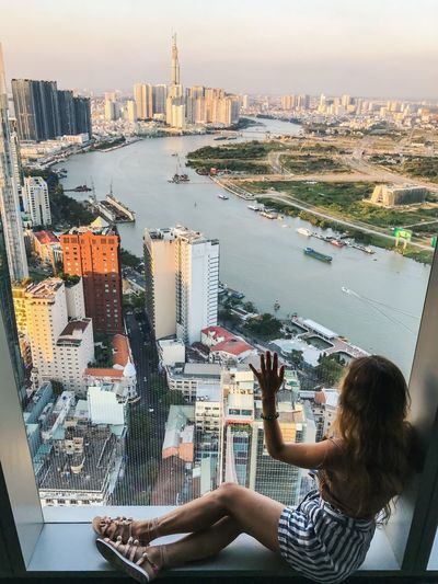 Enjoying The View Observation Point Travel Destinations Glass Wall Window Sitting By The Window Sitting On The Floor Rear View Boats River View Watching Through Windows Building Exterior Architecture Built Structure City Building Cityscape Sky Water Office Building Exterior Real People Landscape Skyscraper Travel Destinations Tall - High Urban Skyline Tower Travel Outdoors Financial District
