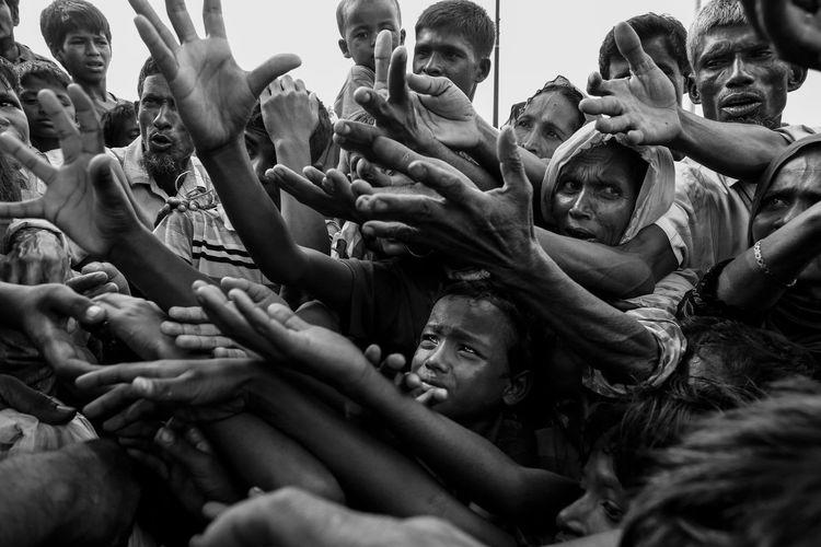Rohingya children stretch their hands out to receive food at a makeshift refugee camp in Cox's Bazar, Bangladesh. Bangladesh Minority Rohingyarefugees Rohingya Blackandwhite Photojournalism Reportage Mushfiqulalam Teknaf Refugeecrisis Migration Mayanmar Refugees EyEmNewHere Eyem Best Shots EyeEm Best Shots Outdoors Crowd Day People Togetherness Human Body Part Human Hand