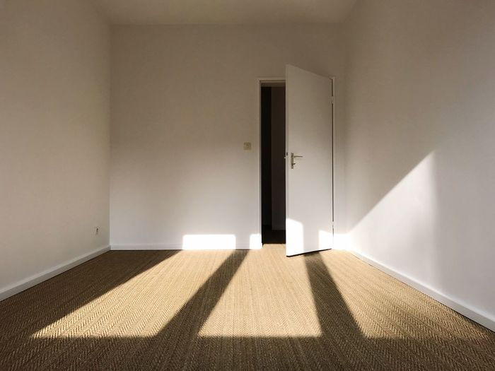 Sunlight falling on empty apartment room, white painted walls and brown carpet