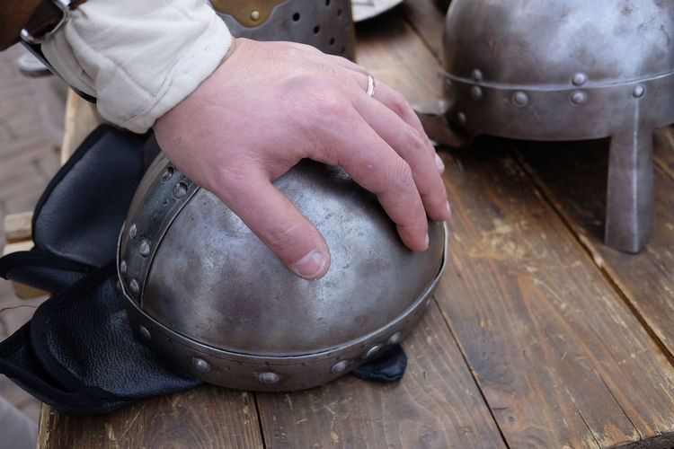 Cropped hand of man touching traditional helmet on wooden table