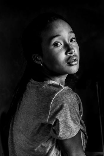 Portrait of smiling girl against black background