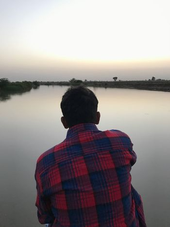 Water Rear View Real People Nature One Person Clear Sky Beauty In Nature Tranquility Reflection Lake Lifestyles Men Scenics Sky Tranquil Scene Leisure Activity Outdoors Standing Sunset Sitting