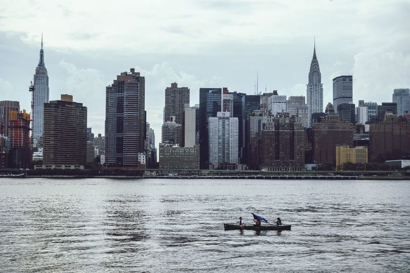 Boat Moving On River In Front Of Cityscape Against Sky