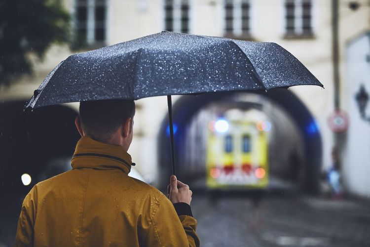 Rear view of man with umbrella on wet street