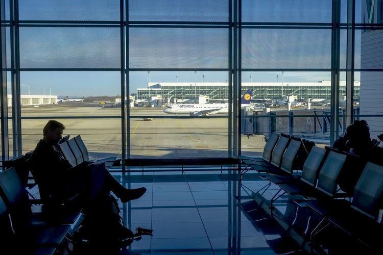 People sitting in airport runway seen through window
