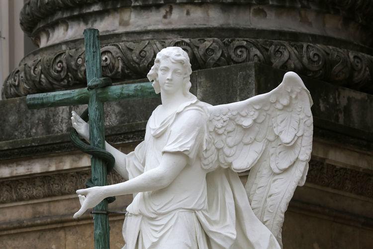 Angel statue with cross at karlskirche in karlsplatz