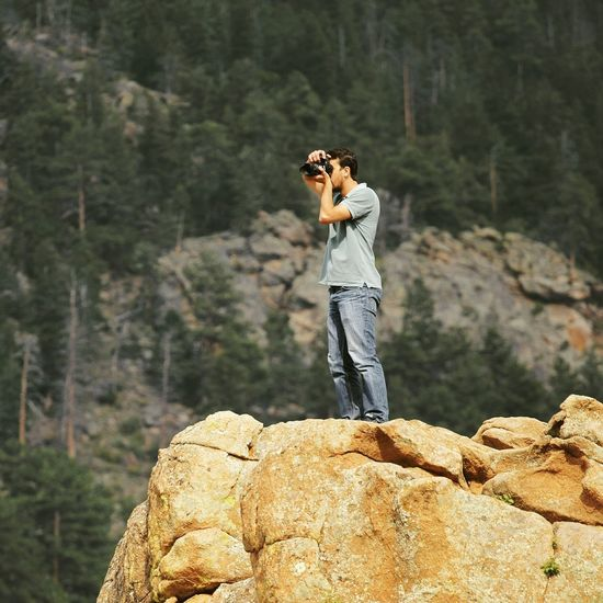Man photographing with camera while standing on rock against trees in forest