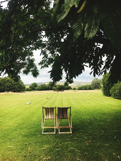 Empty chair on field against sky