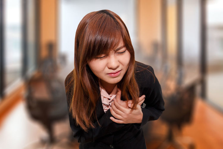 Close-up of young woman suffering from chest pain