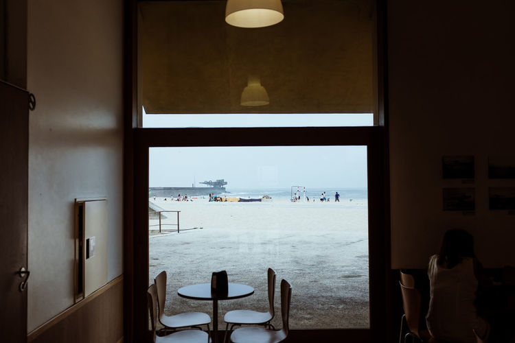 High angle view of table and chairs by window at beach restaurant
