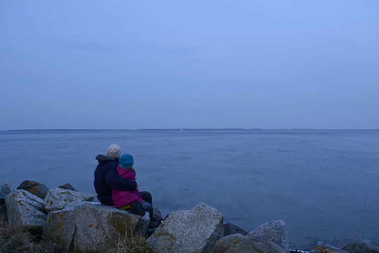 Rear View Of Mother And Daughter On Rocks At Beach