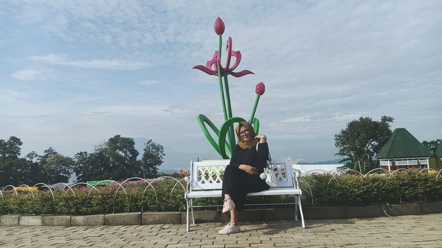 Full length of woman sitting at park against sky
