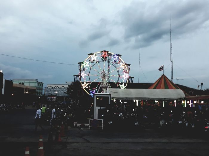 People in amusement park against sky in city