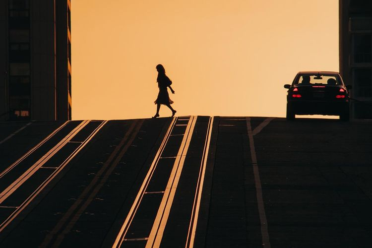 Woman in a dress crossing a street in San Francisco, USA Women Dress Street Streetphotography Sunset Golden Hour The Art Of Street Photography Full Length Politics And Government Silhouette Urban Scene Cityscape Skyscraper Tall - High Office Building City Location