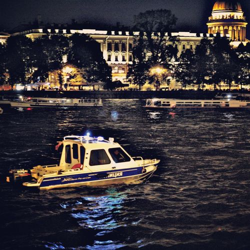 Boat in river against illuminated buildings at night