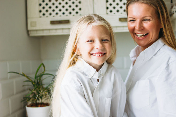 Happy blonde long hair mom and daughter in the kitchen, healthy lifestyle