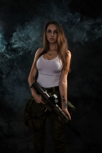 Adult Beautiful Woman Black Background Fashion Front View Gun Hair Hairstyle Holding Indoors  Long Hair Looking At Camera One Person Portrait Smoke - Physical Structure Standing Studio Shot Three Quarter Length Weapon Young Adult Young Women