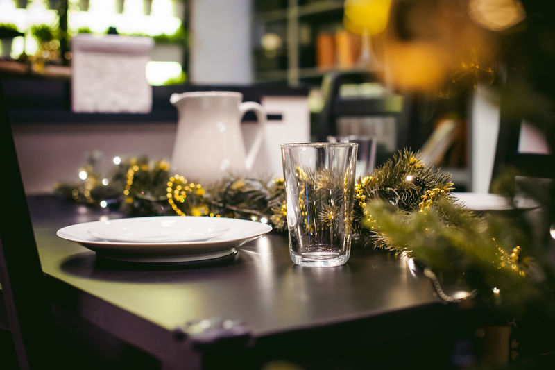 Close-up of plate and drinking glass with christmas decorations on table