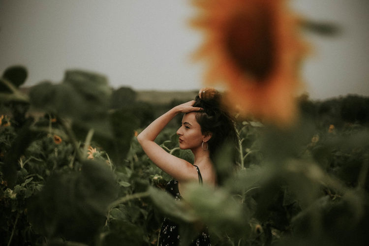 Young Woman Standing Amidst Sunflowers On Field