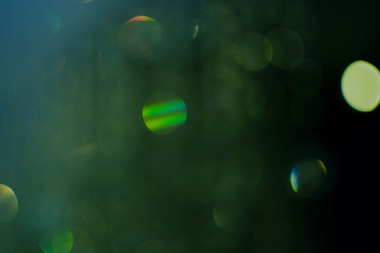 Green tone bokeh of decorative hanging lights in the night Blurred Bright Decor Glitter Green Green Color Hanging Light Abstract Bokeh Defocused Glowing Night Party