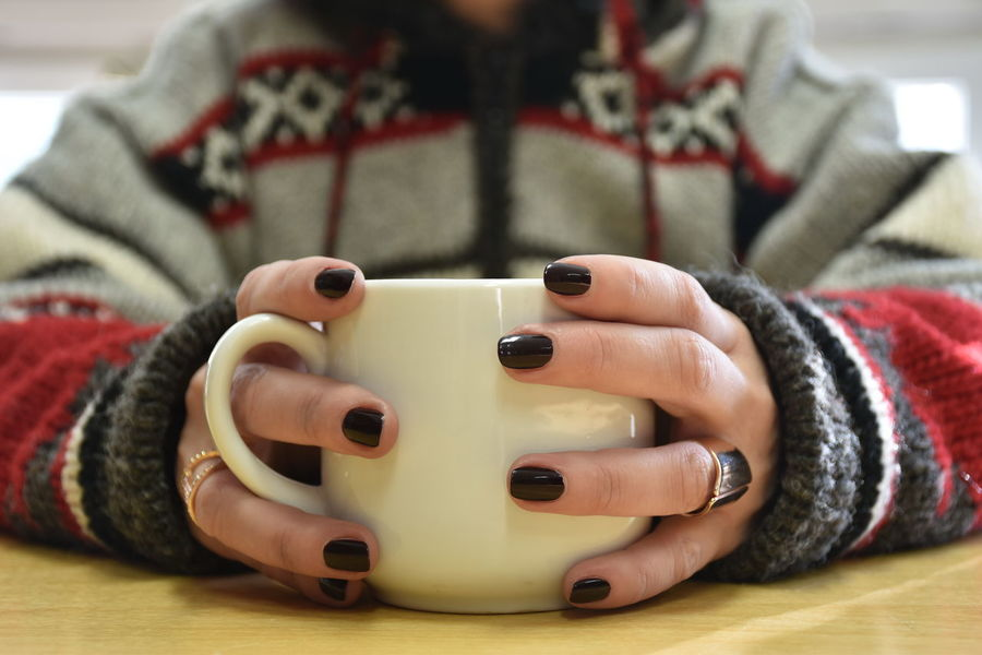 Adult Close-up Coffee Cup Cup Finger Focus On Foreground Front View Hand Holding Human Body Part Human Hand Indoors  Leisure Activity Lifestyles Midsection Nail Nail Polish One Person Real People Sitting Sweater Warm Clothing
